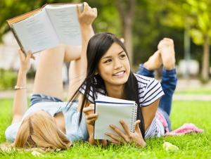 students reading books and laying on grass